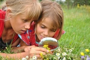 girls-with-magnifying-glass-look-at-flower-140002277